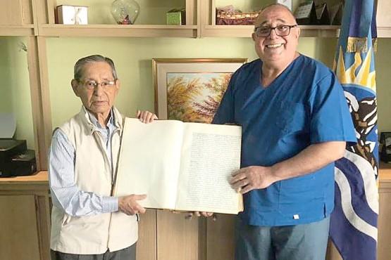 El Dr. José David junto al Dr. Juan Utrilla sosteniendo el primer libro de actas del Colegio Médico de Santa Cruz.