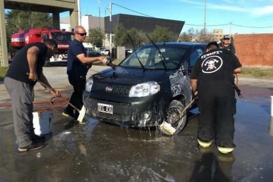 Bomberos lavan autos a cambio de golosinas