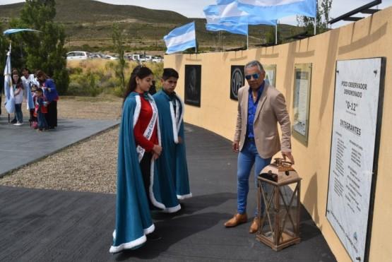 """Jorge Soloaga, acompañado por los jóvenes soberanos de la localidad, Luisina Romero e Iván Saldivia, depositaron el farol """"luz de vida!"""" junto a la placa de mármol que recuerda los nombres de pioneros ypefianos."""