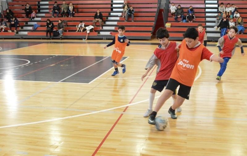 Los chicos disputando la pelota en pleno partido.