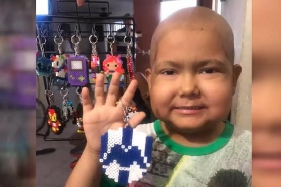 El niño vende llaveros para costear el tratamiento contra el cancer.