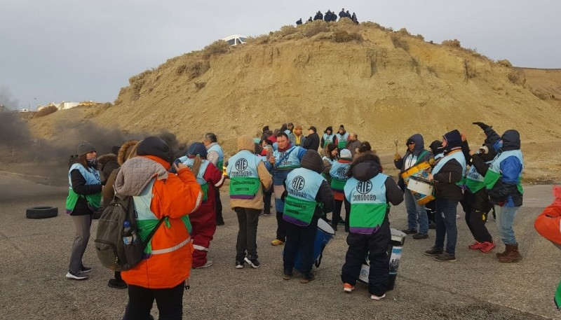 Los empleados reclaman y de fondo, en la montaña, los efectivos policiales.