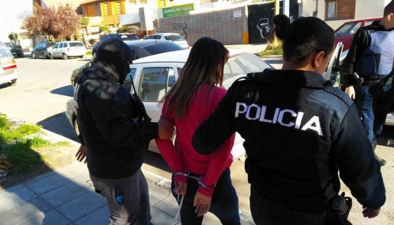 Personal policial llevando detenida a una de las mujeres.