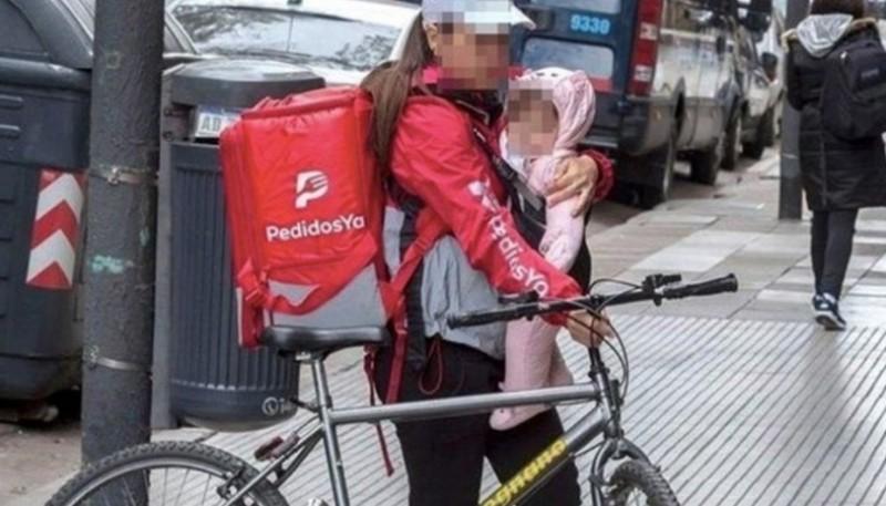 La repartidora fue fotografiada con su hija en brazos y se hizo viral.