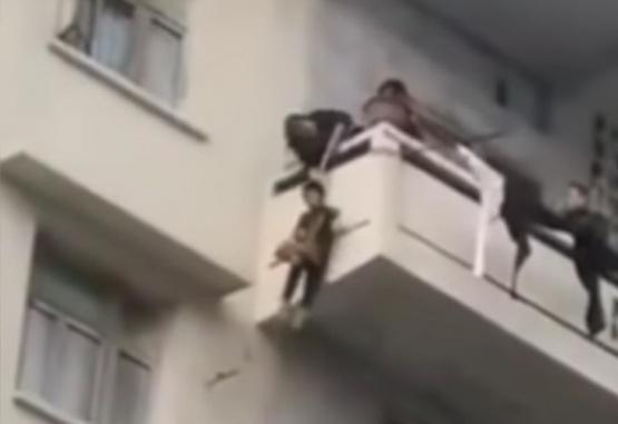 Captura de video del momento en que la pareja hace bajar a su nieto por el balcón.