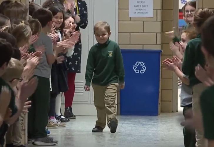 Captura de video del momento en que el nene de 6 años regresa a su colegio y es ovacionado por grandes y chicos.