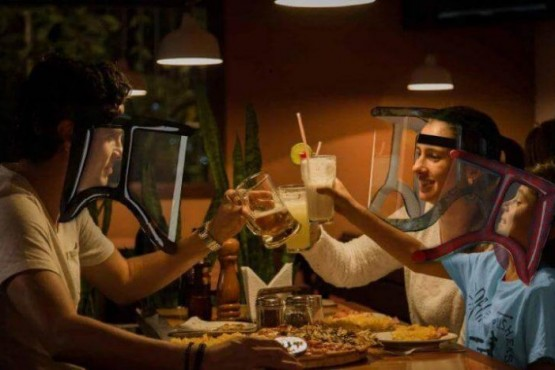 Diseñaron un protector facial inflable que permitiría juntarse a comer sin riesgos