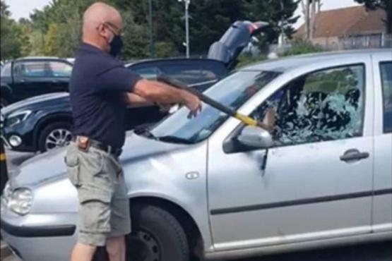 Un hombre rompe la ventana de un auto para rescatar a un perro encerrado