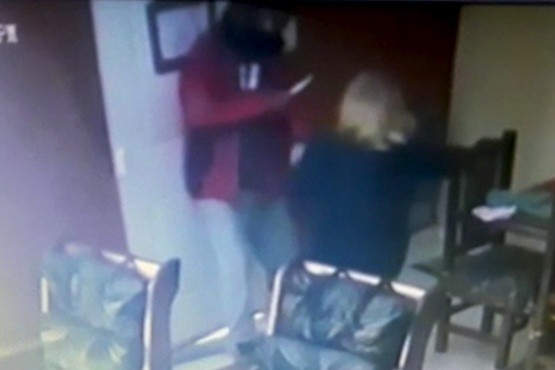 Captura del video de la cámara de seguridad donde se ve al sujeto amenazando con un cuchillo y arrastrando de los pelos a la mujer.