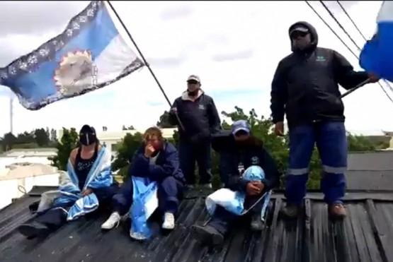 Los trabajadores trepados en el techo.